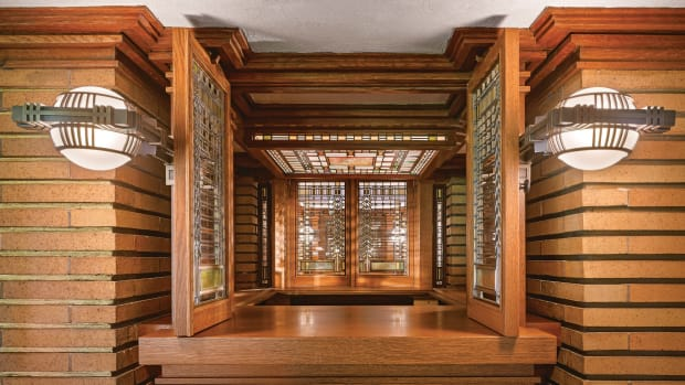 """The view of """"light unit"""" shows the restored wood cabinetry and interior brick work with gilded mortar joints. Pairs of replica light sconces flank casement windows with Wright designed art glass."""