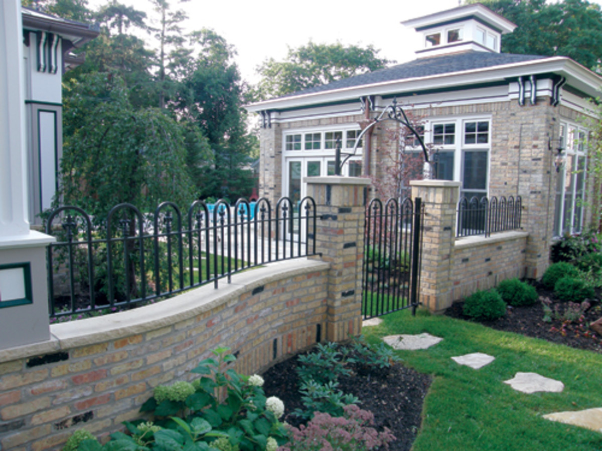 This fence was fabricated by Mueller Ornamental with all solid bars, cast-iron points and hand-forged scrolls on the gate arch.