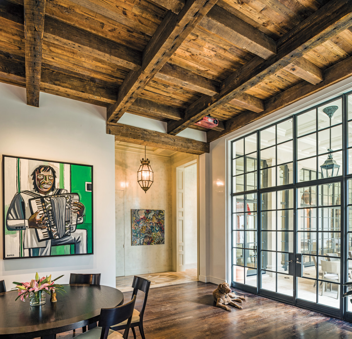 Salvaged beams grace the ceiling in the breakfast room while steel windows frame the view of the loggia.