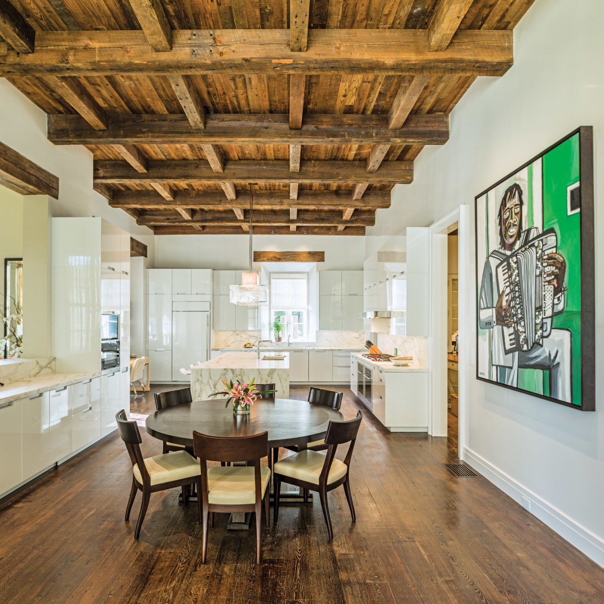A modern Italian kitchen juxtaposes the old beams and smooth plaster walls in the kitchen.