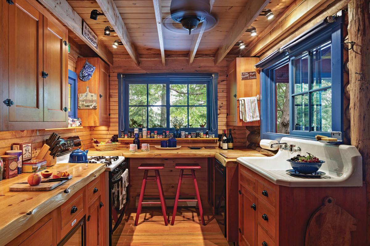 The small kitchen has a pass-through window so the cook can serve food to those on the screened-in porch. The countertops are slabs of pine, and the wooden cabinets are in a traditional 19th-century style.