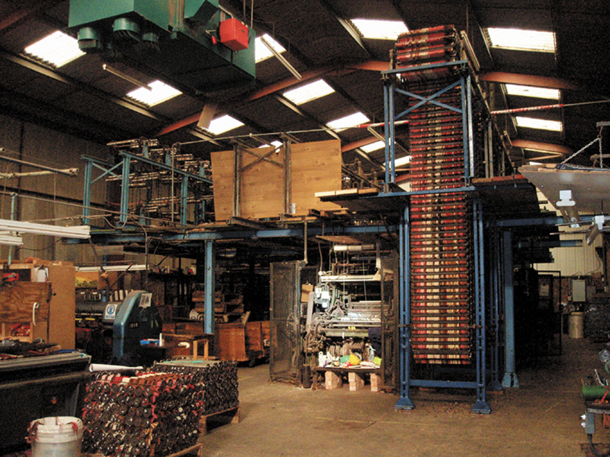 The Living Looms workshop with yarn loaded on to the loom for the first half of the pattern and, on the left, spools being set for the second half. The yarn is set on each spool with colours in the correct position for one row of the design. 1480 spools were set for the Hampton carpet. Photo: courtesy of David Luckham Consultants, Ltd.
