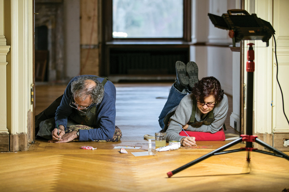 Conservators work to repair the wood floors in between Fair Lane's living and dining rooms.