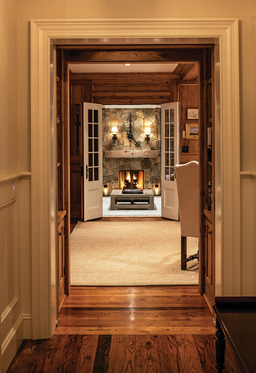 The entry extends through three enfiladed spaces and culminates at a framed fireplace.