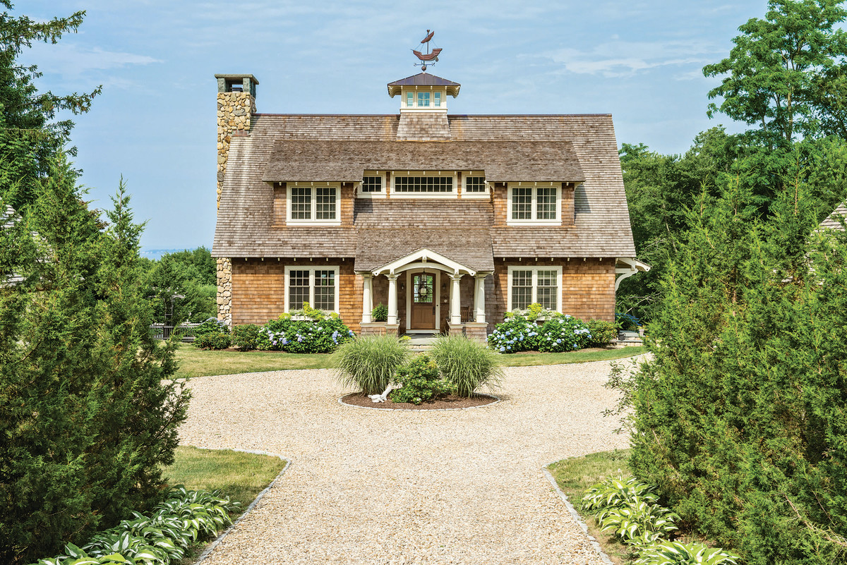 Architect David Andreozzi designs a Shingle-styled house with wood roof with traditional rafter tails in Rhode Island.