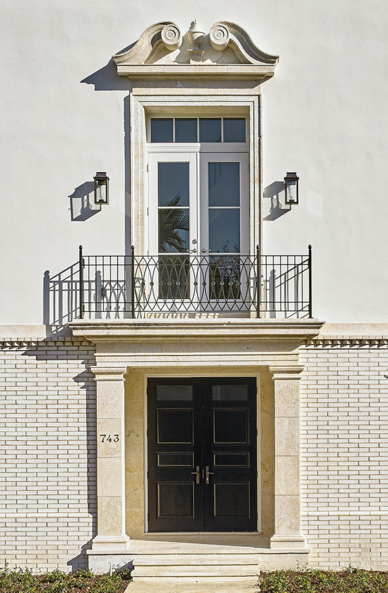 The ram's head pediment at the piano nobile balcony emphasizes the entry portico of the two corner townhouses that front the avenues.